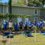 A team of Boy Scouts stands behind raised garden beds they built for the CHILD Center
