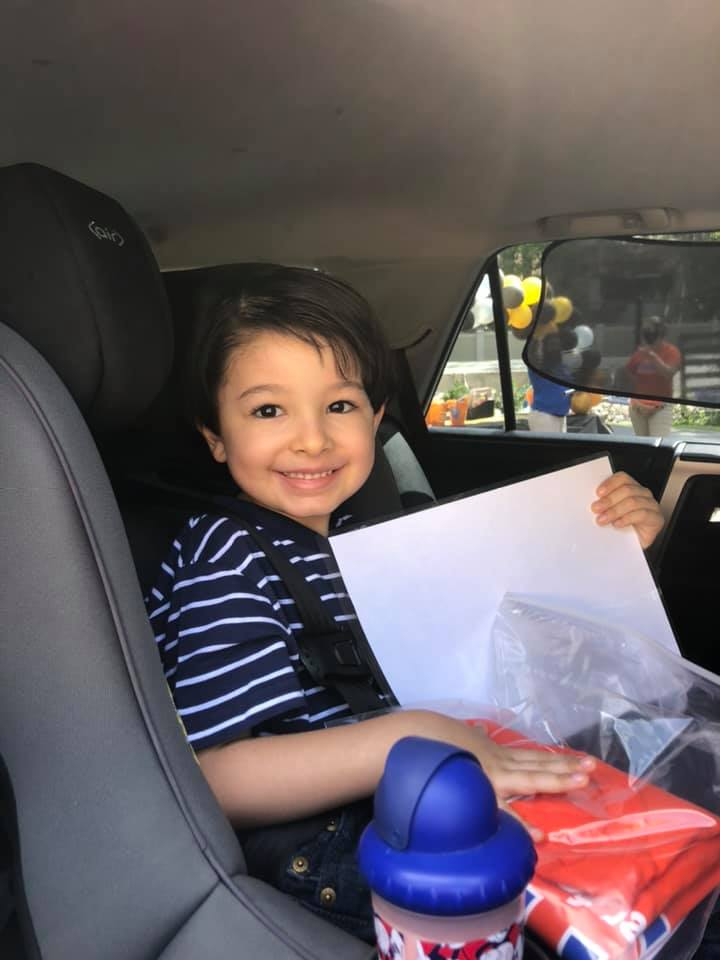 "A 2020 grad sits in a car and holds a ""Bachelor of Preschool"" diploma"