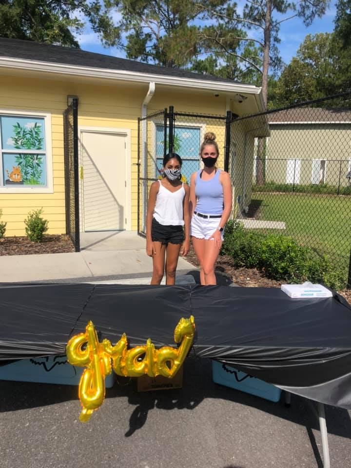 "Two young ladies stand behind a table with a balloon reading ""grad"""