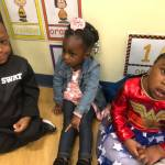 Three students sitting together on the CHILD Center floor