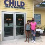 Two young ladies standing in front of the CHILD Center facility