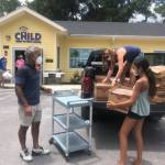 Three people unloading boxes of food from a truck