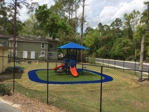 A playground structure with orange slides and platforms for climbing sitting on top of soft green and blue padding