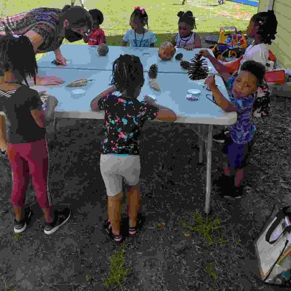 A group of students gathers around an outdoor table enjoying the April 2021 weather and learning about gardening