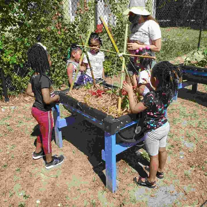 A group of CHILD Center students and their instructor stand around a raised garden bed during April 2021 garden programming