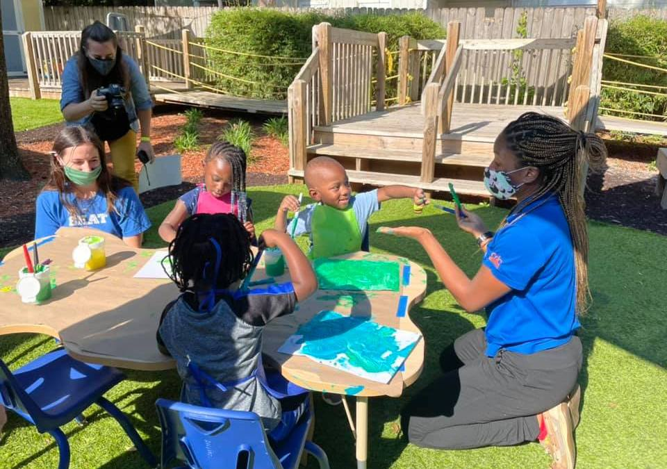 CHILD Center students interact with their instructor while fingerpainting outside in April 2021