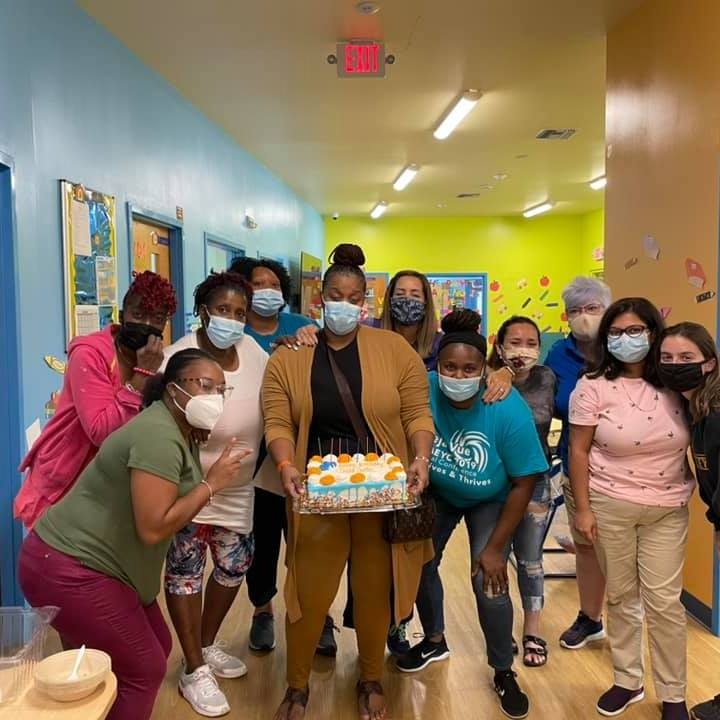 CHILD Center staff stand around an orange and blue birthday cake to celebrate the third birthday of the Center