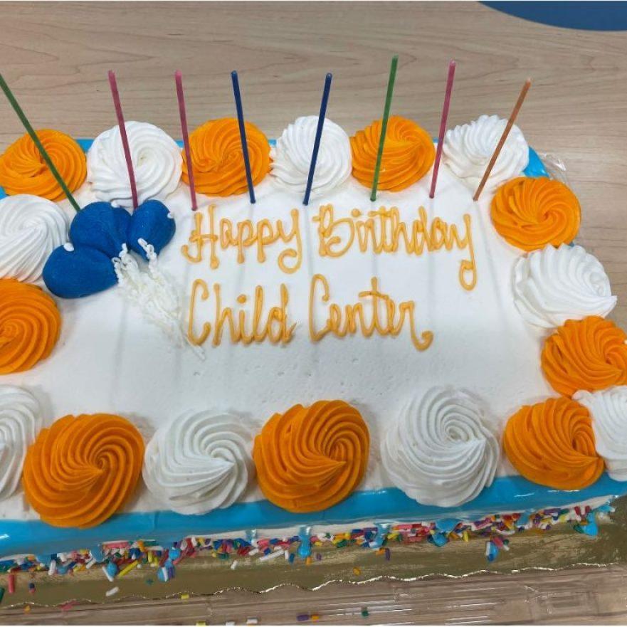 "An orange, blue, and white birthday cake that reads, ""Happy Birthday CHILD Center"""