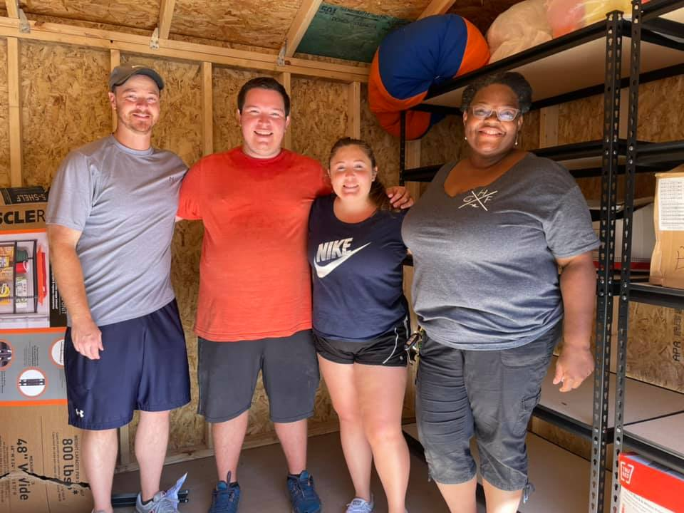 Four volunteers stand together inside the storage shed at the CHILD Center on fence-building day