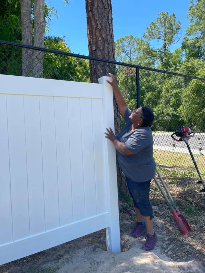 A volunteer helps put the finishing touches on the new fence at the CHILD Center
