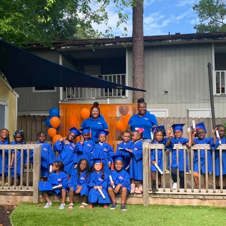 The Summer 2021 graduates pose in a large group in blue caps and gowns. CHILD Center staff stand with them.