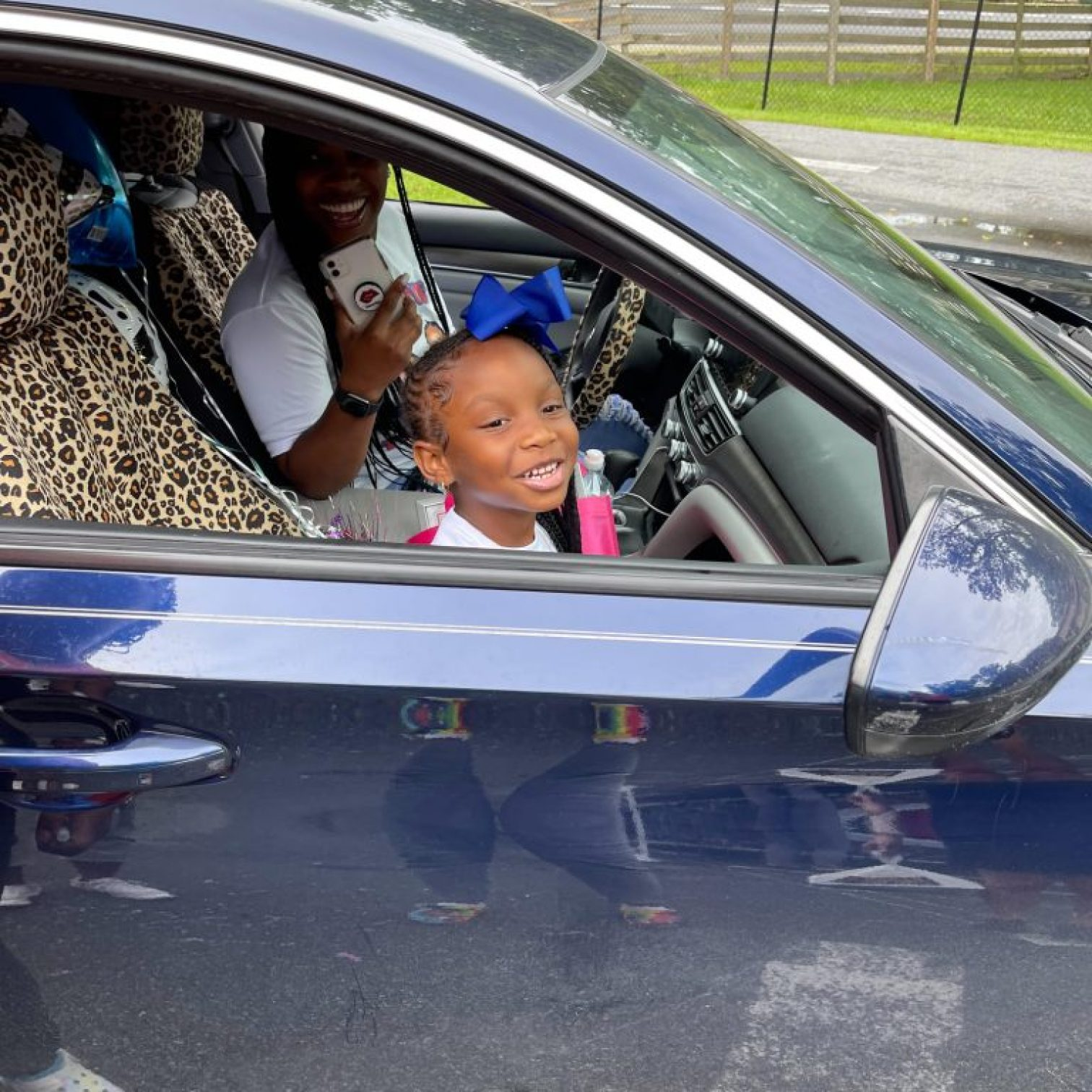 """A child smiles out the window of a car during the Summer 2021 """"Buzz-By"""" graduation celebration"""
