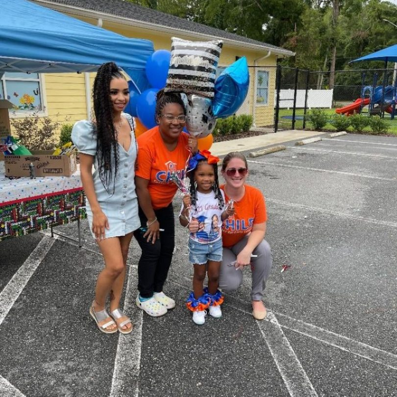 """A small child poses with CHILD Center staff members during the Summer 2021 """"Buzz-By"""" graduation celebration"""