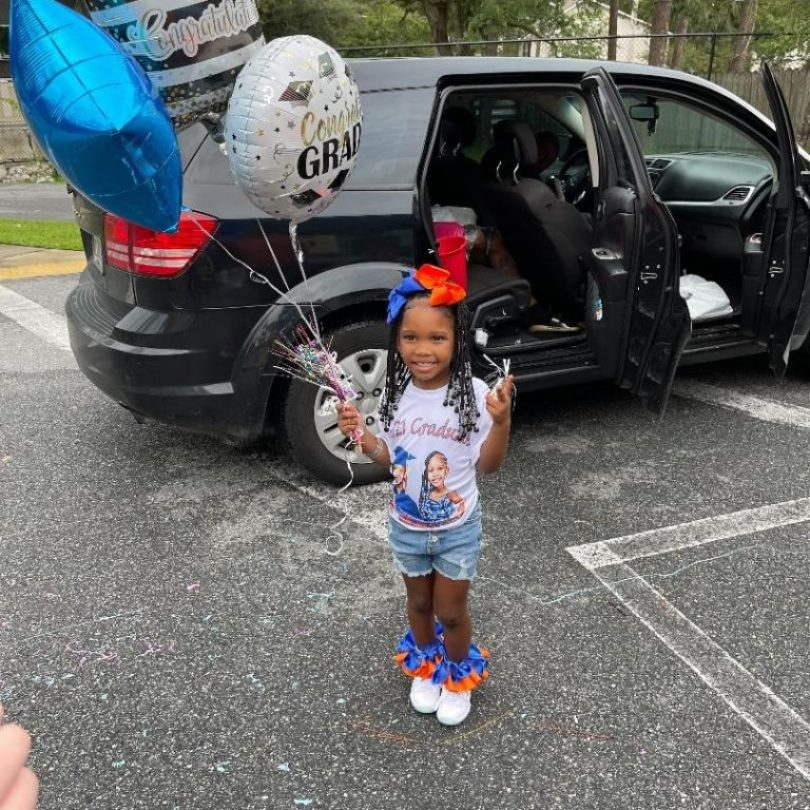 """A child stands in the CHILD Center parking lot holding helium balloons with """"Congrats Grad"""" messages printed on them"""