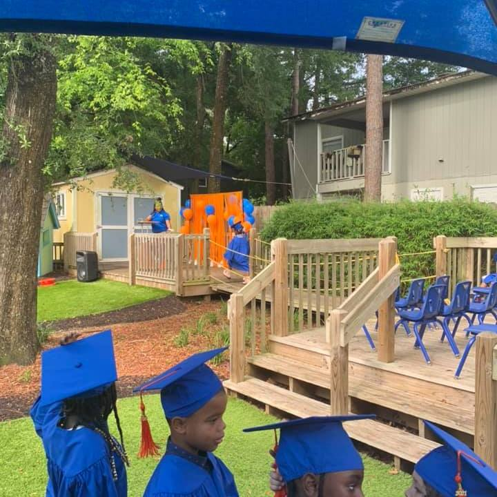 Summer 2021 CHILD Center graduates stand in a line wearing caps and gowns during the outdoor graduation ceremony