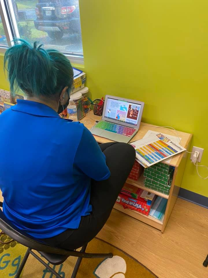 A CHILD Center staff member reviews training materials on a laptop during the Summer 2021 teacher training