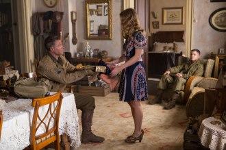 A transaction among Brad Pitt, Alicia Von Rittberg, Logan Lerman, and Anamaria Marinca in David Ayer's FURY.