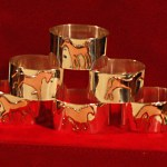 Six sterling silver serviette (napkin) rings with little copper horses on them, all different.