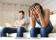 stock-photo-angry-boyfriend-and-sad-girlfriend-at-home-couple-worried-after-argument-453509824