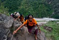 Stranded Indian pilgrims make their way up a mountain after a section of road was washed away in Govind Ghat