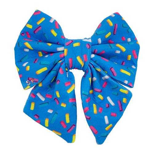 Blue sprinkle sailor bow tie with a blue background and rainbow sprinkles across design