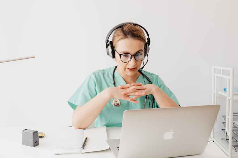 woman in scrub suit sitting in front of a laptop on a video call