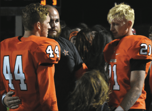 Coach Brad Chesshir consoles seniors Austin Gibbs (44) and Dalton Smead following the Scrappers' 53-28 playoff loss to Pea Ridge Friday night at Scrapper Stadium.