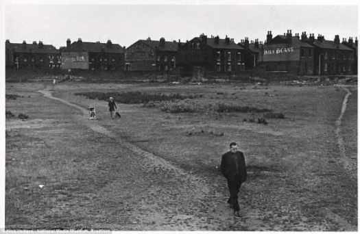 Пустошь: мужчина, засунув руки в карманы, уходит от унылых домов ленточной застройки в Лидсе в июле 1970 года, за ним женщина выгуливает свою собаку, рядом с ней детская коляска.