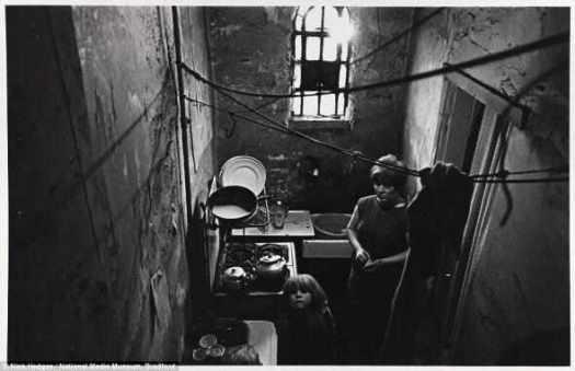 Голод: женщина и ее ребенок смотрят из кухни муниципальной квартиры в трущобах в Balsall Хит, Бирмингем в ноябре 1969. года Над ними верёвка для сушки белья, привязанная к открытым трубам водопровада, в сырой комнате.