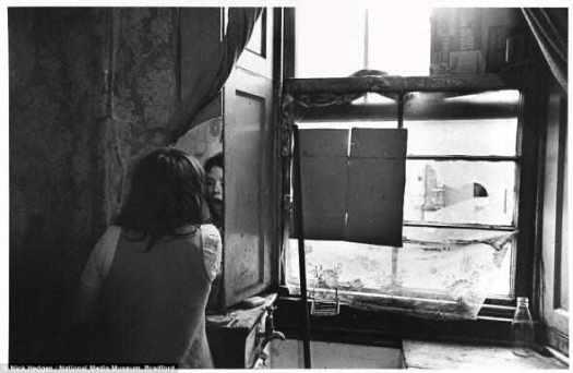 Стремление к нормальности: Вглядываясь в осколок зеркала на стене, молодая женщина наносит макияж в подвальном помещении в Глазго, где она живёт, в октябре 1970 года. Рядом с ней из крана медленно капает в грязную раковину. Свет льется через разбитое окно, наспех закрытое картоном, от выброшенной коробки от хлопьев.