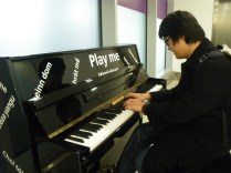 Alex playing a piano in the London Heathrow airport