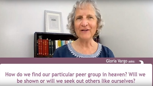"Karin sits at her desk in front of a bookshelf. A question from audience member Gloria Vargo appears across the bottom of the screen, reading: ""How do we find our particular peer group in heaven? Will we be shown or will be seek out others like ourselves?"""