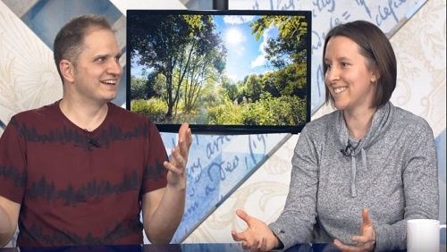Curtis and Chelsea sit together at the anchor desk, in front of an image of beautiful green trees and blue skies.