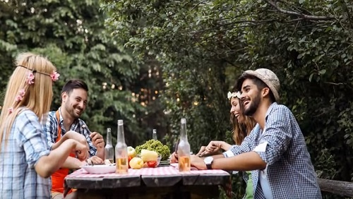 A group of four people eat a meal together outside at a picnic table. They look happy and are laughing.