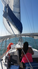 Dana takes the helm as we put Miami behind us and stretch out across Biscayne Bay under full sail on a broad reach.