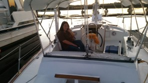 Here's dana in the cockpit about 10 days before we departed New Bern. The photo is a little fuzzy, but you can see the new engine gauges on the starboard side, next to the speaker. The steering pedestal is in the middle of the restoration process here. You can also see the new bimini top, made from PVC 1x2 ribs, stainless pipe clamps, and 4x8 fiberglass panels purchased at Lowes. It survived hurricane Matthew.
