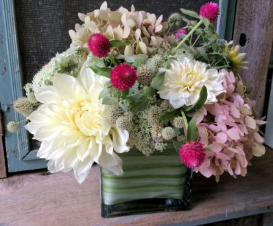 Glass cube filled with garden flowers of dahlias, hydrangeas,gomphrena and rattlesnake master