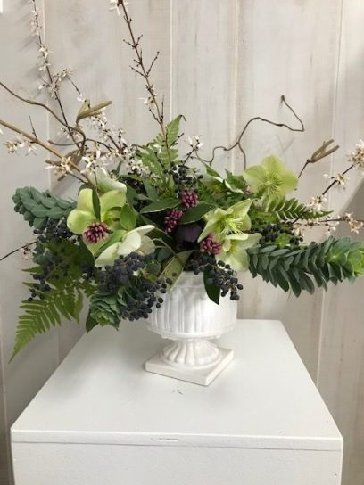 Daphne , white forsythia and spurge in a small pedestal vase