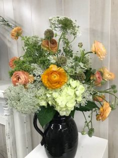 Queen Anne's lace and peach ranunculus shine in this black ceramic pitcher