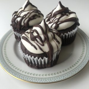 Three chocolate cupcakes with white buttercream and chocolate drizzle placed on a plate