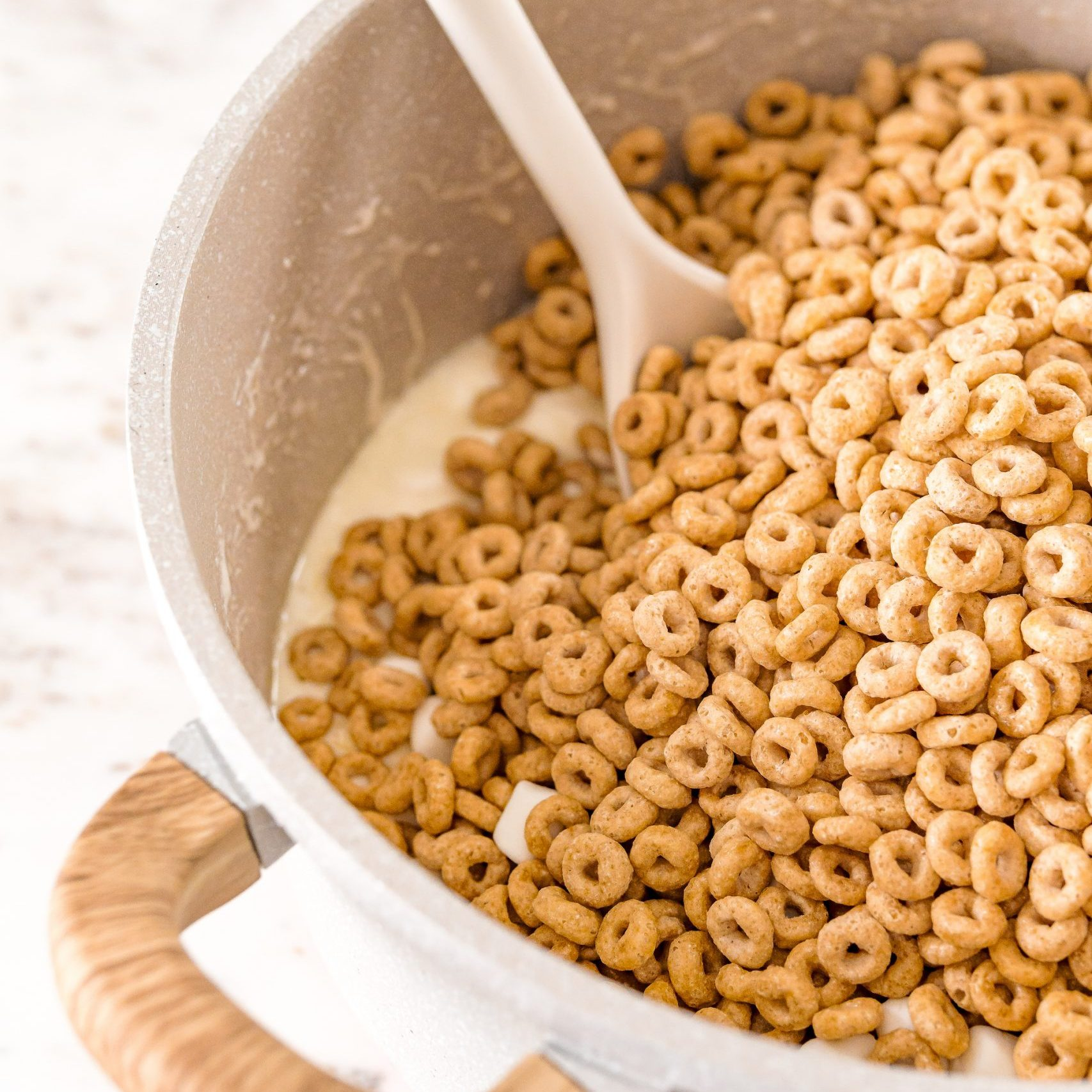 mixing cheerios with melted marshmallows in a pan picture