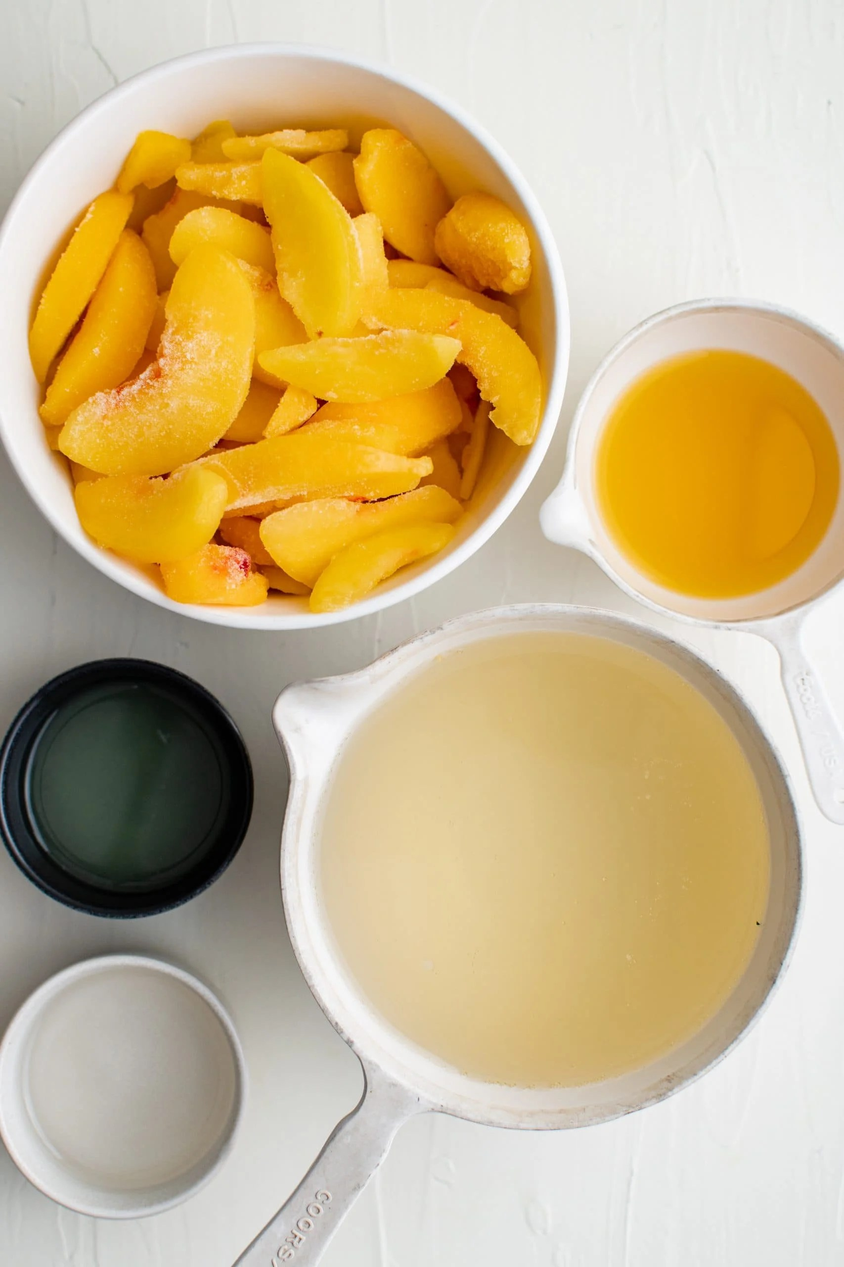 picture of frozen peaches, champagne, simple syrup and sugar on a table