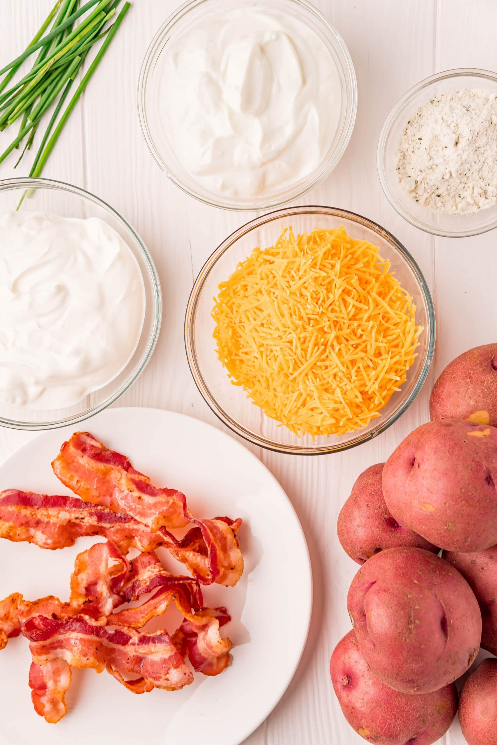 picture of ranch, mayonnaise, potatoes, bacon, cheese, and chives in plates on a table