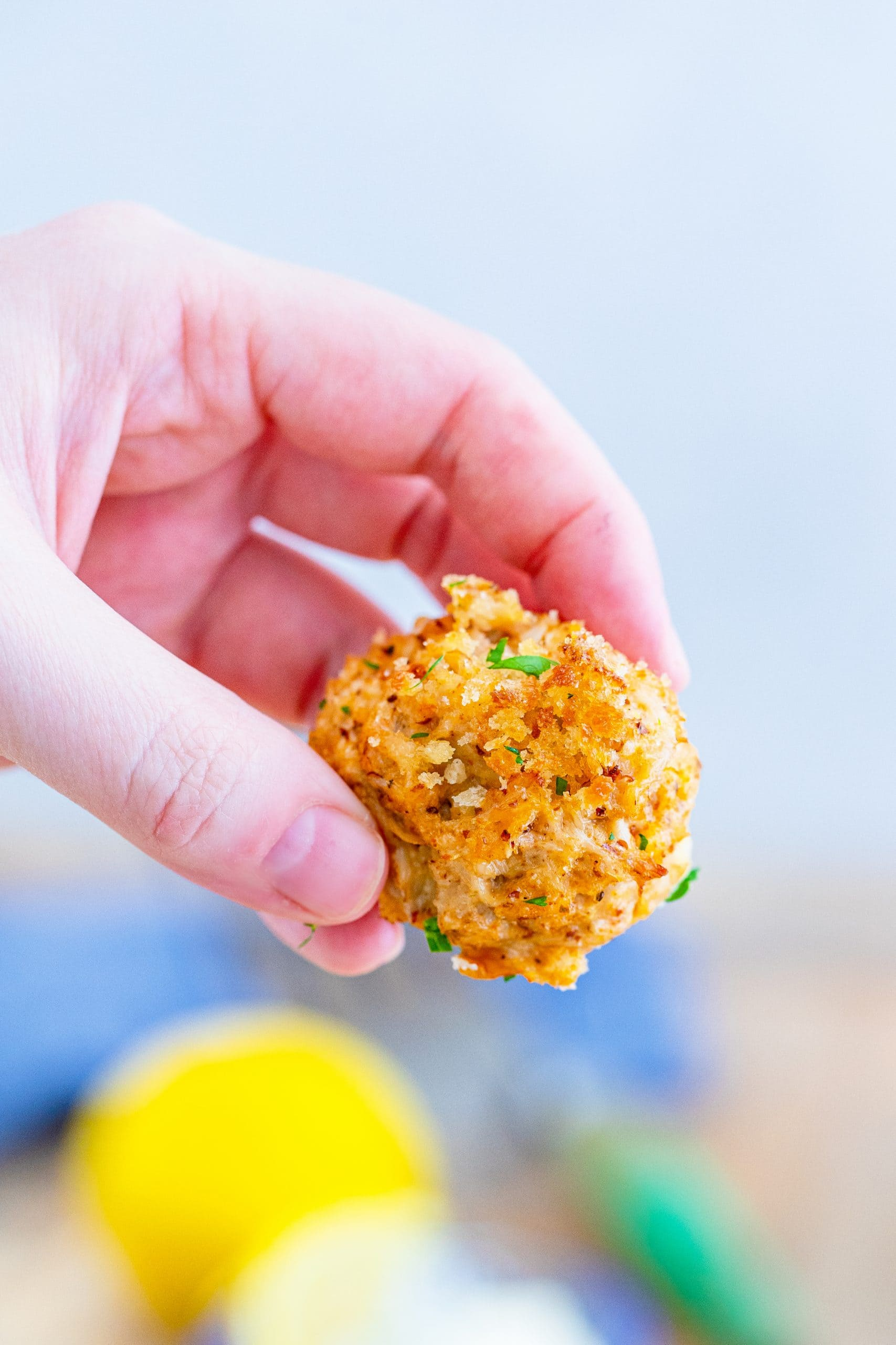picture of a hand holding a crab cake