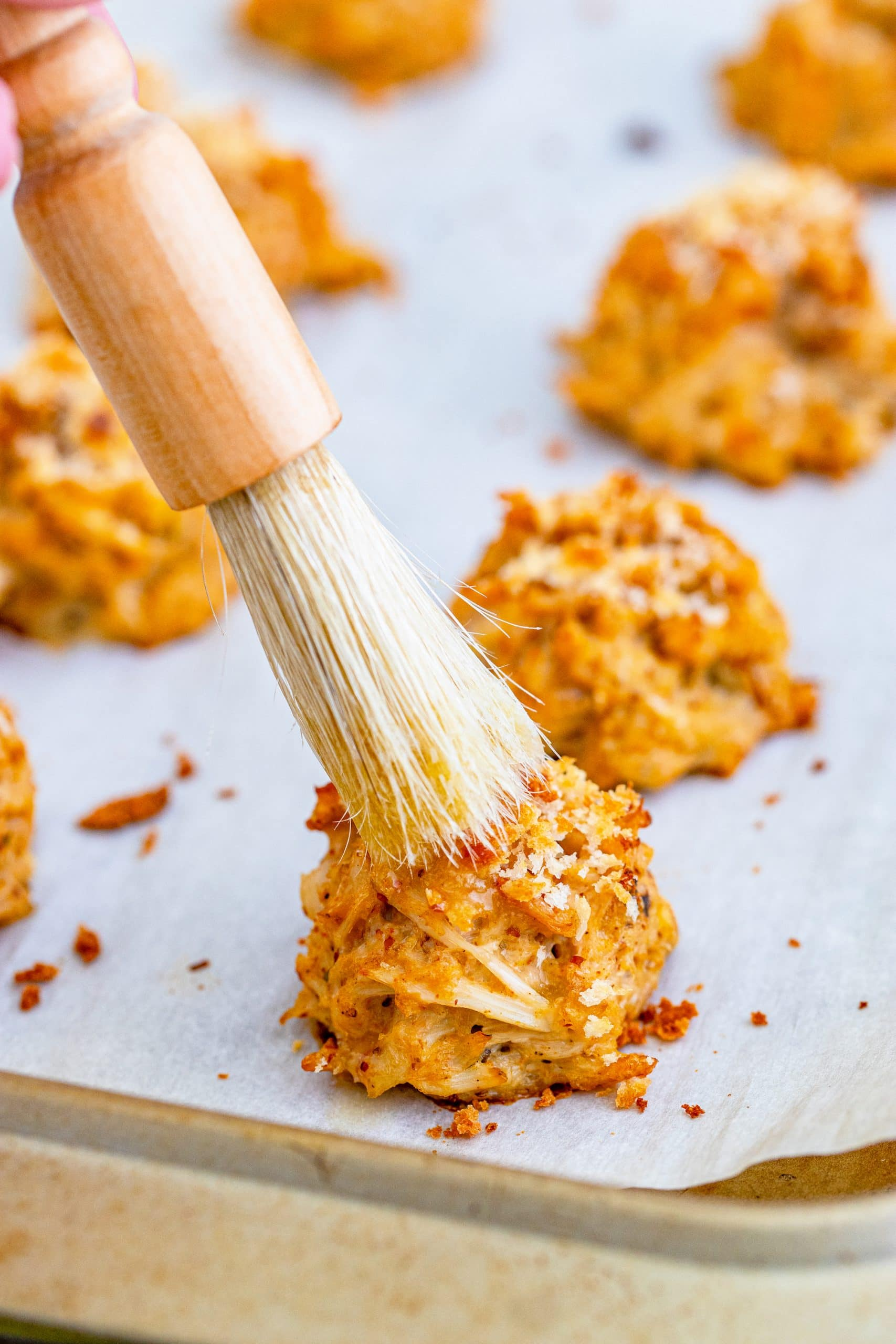 picture of a brush brushing butter onto a crab cake