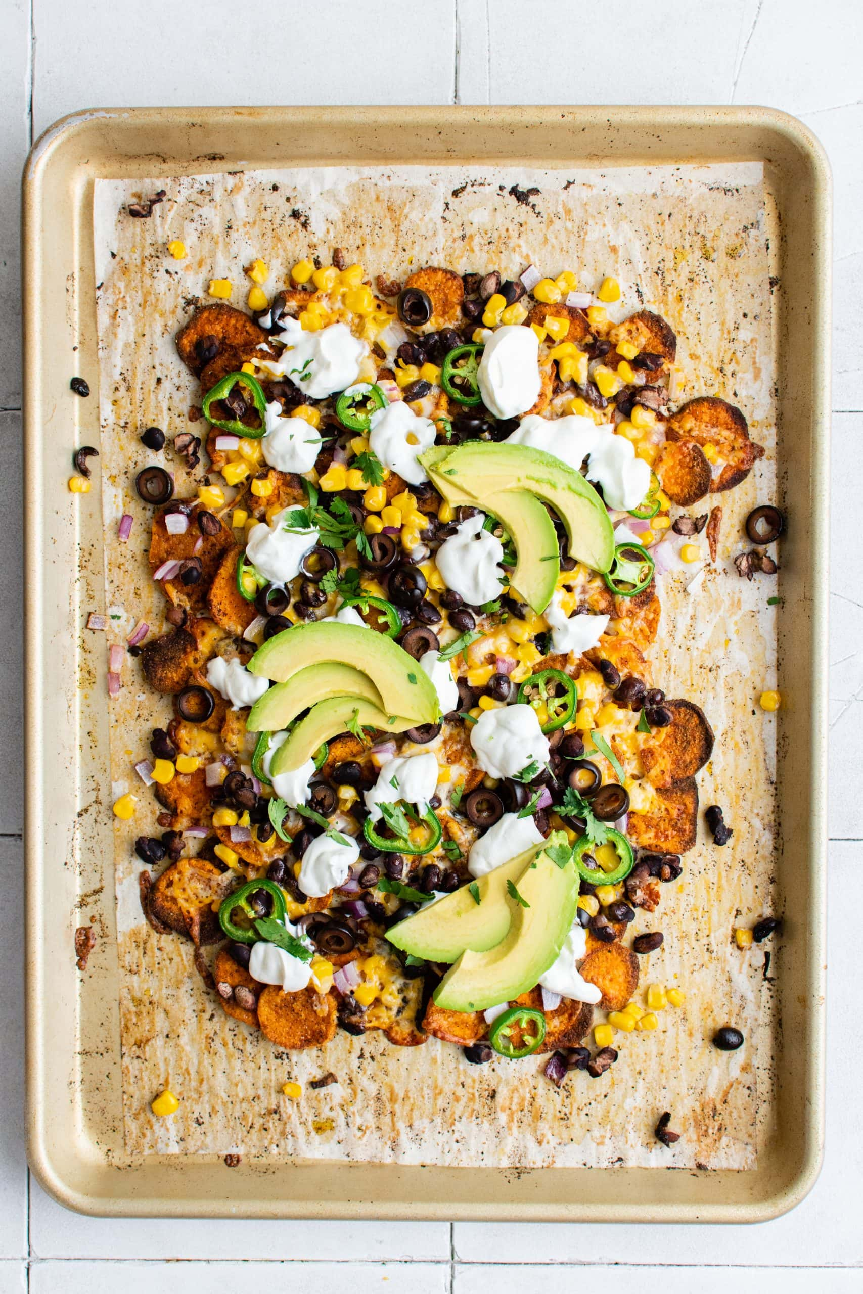 picture of sweet potato chip nachos on a plate with jalapenos, beans, corn, cheese, sour cream, avocados, and sliced limes