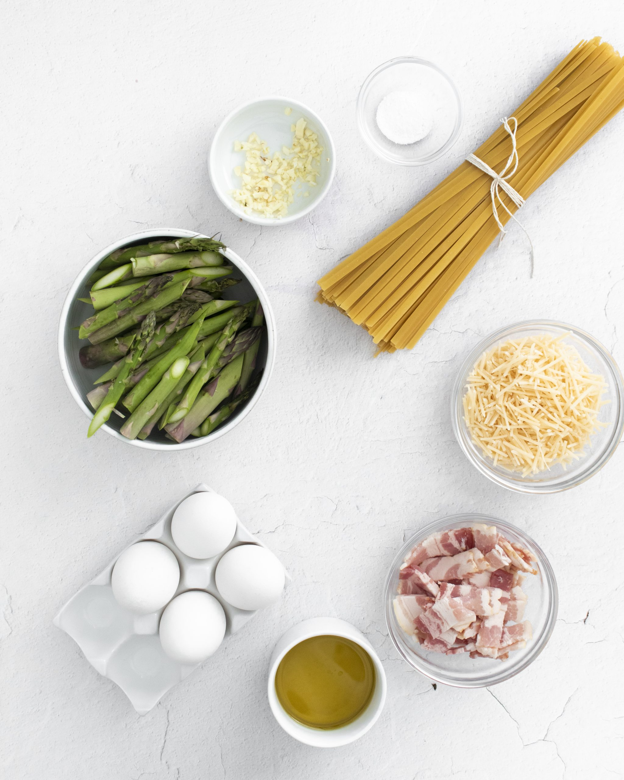 picture of asparagus cheese egg bacon pasta and olive oil on a table