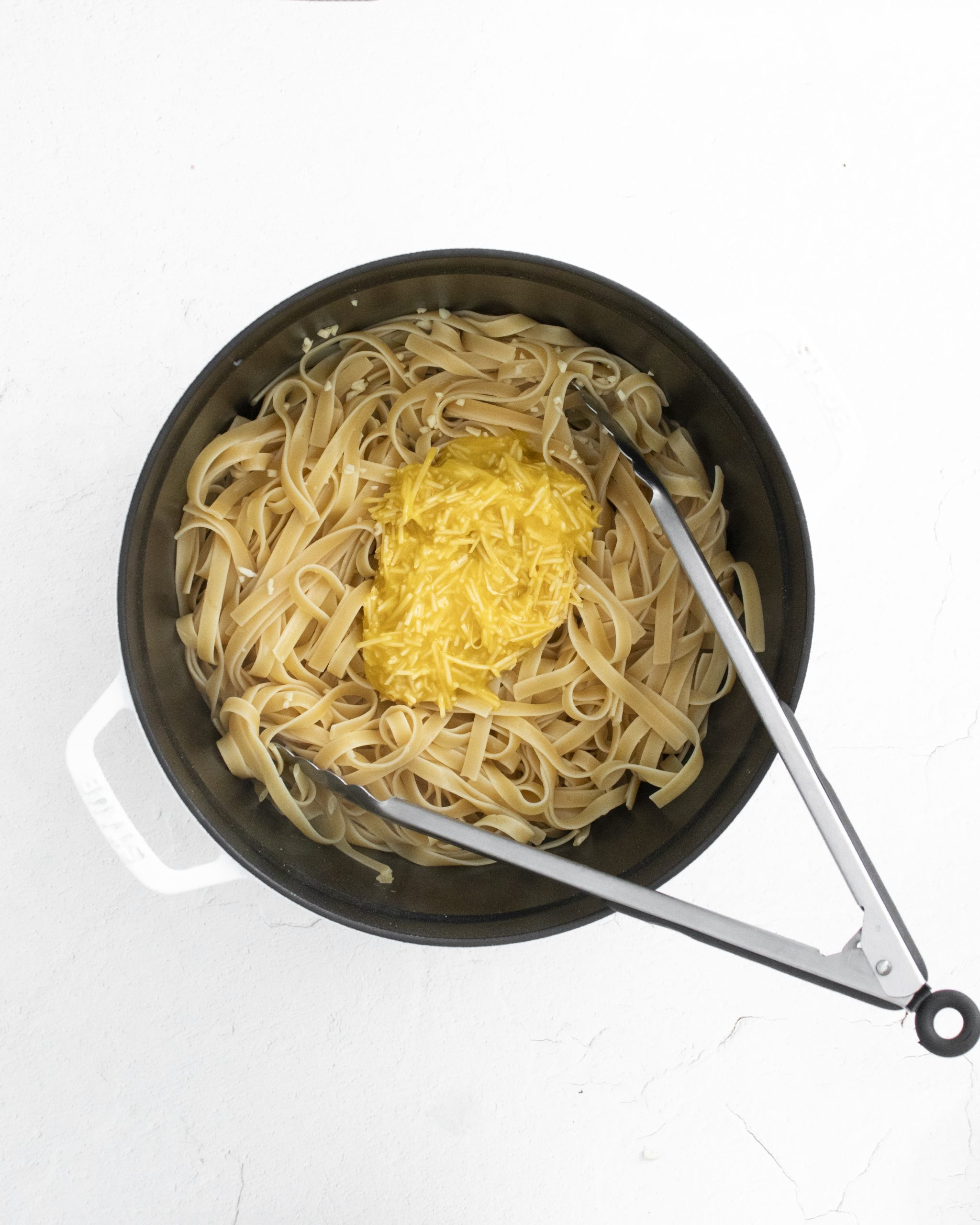 picture of carbonara being poured onto cooked pasta noodles