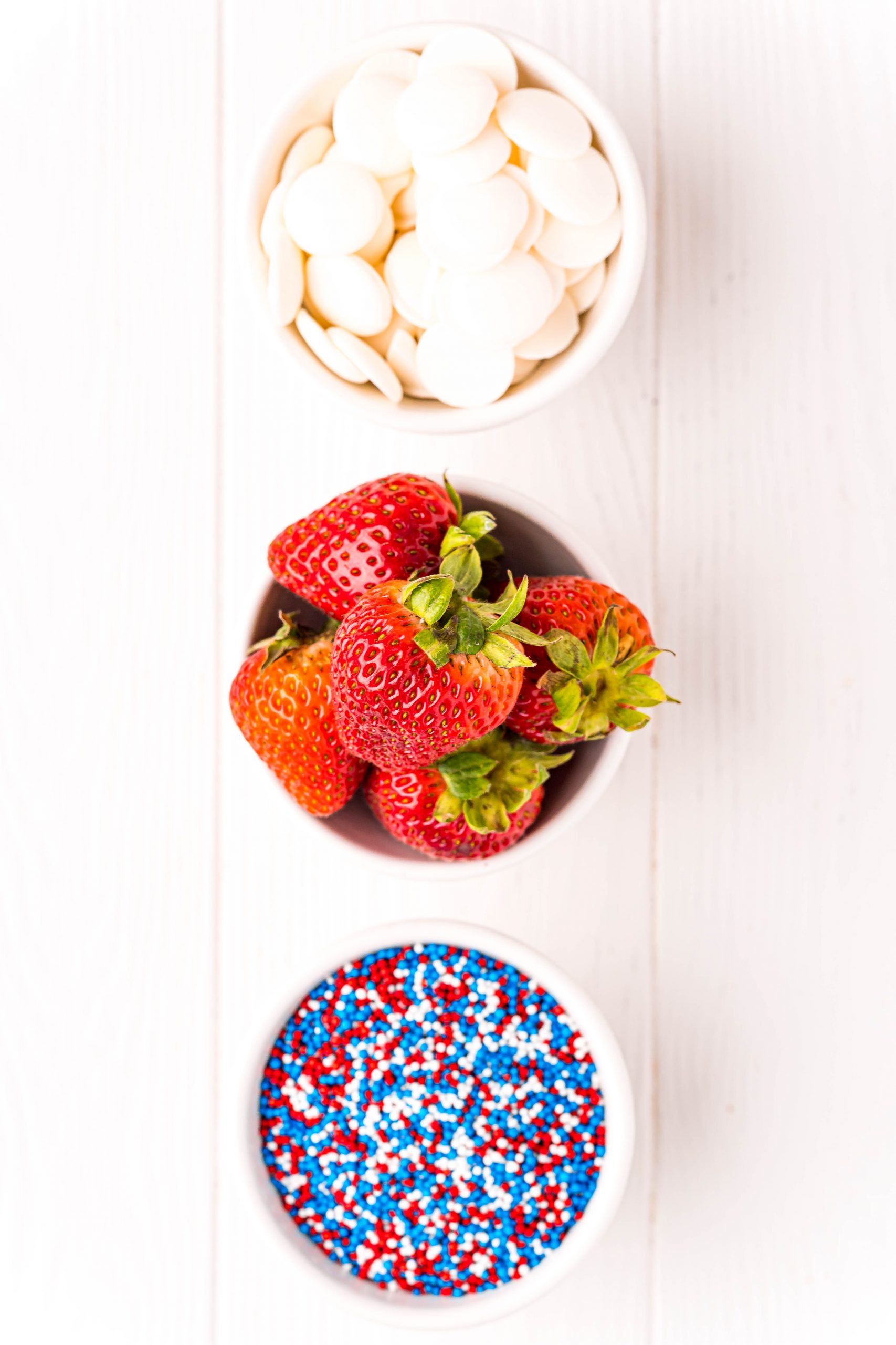 picture of white chocolate, strawberries, and sprinkles on a table