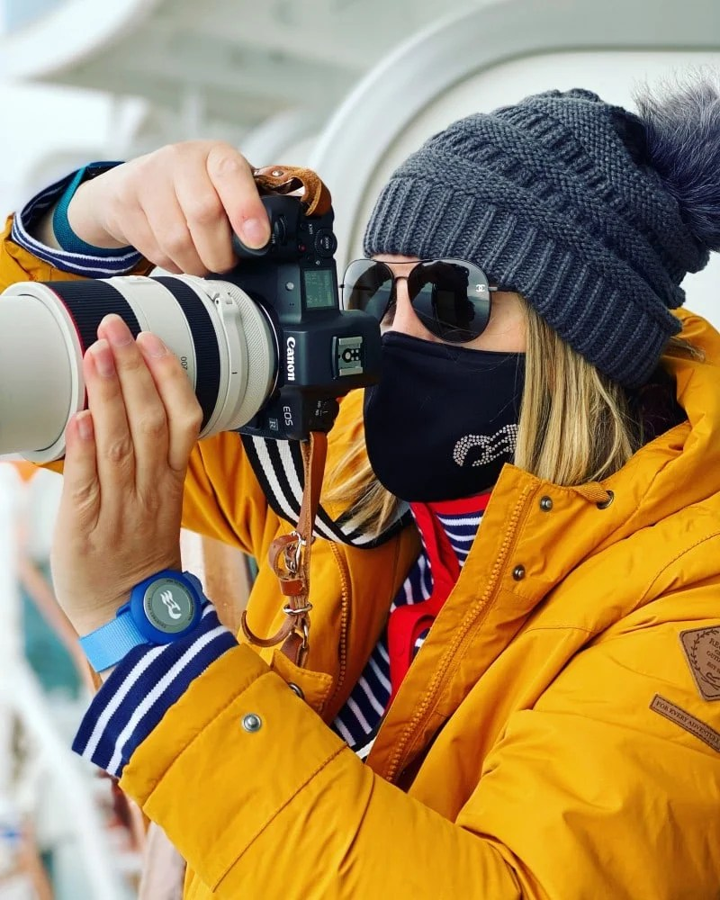 picture of woman in yellow jacket holding a camera with a princess cruises face mask